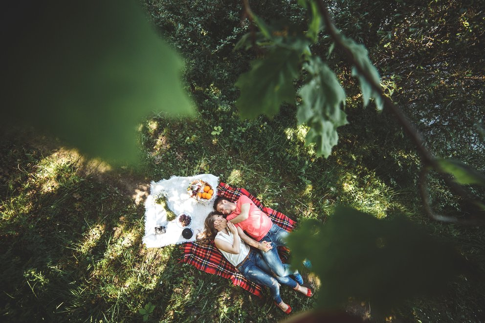 ein Pärchen liegt auf der wiese und picknickt