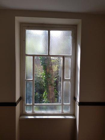 Halbdunkles Treppenhaus, Blick aus Fenster