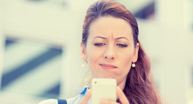 Closeup side profile portrait upset sad skeptical unhappy serious woman talking texting on phone