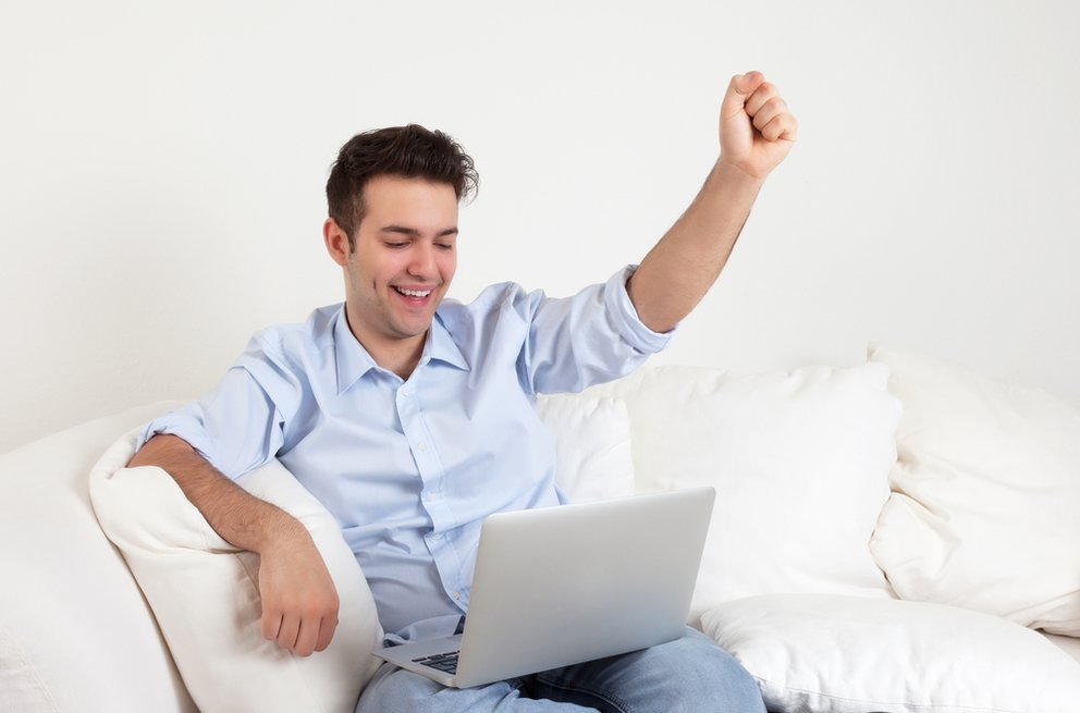 Cheering hispanic guy with notebook on a sofa