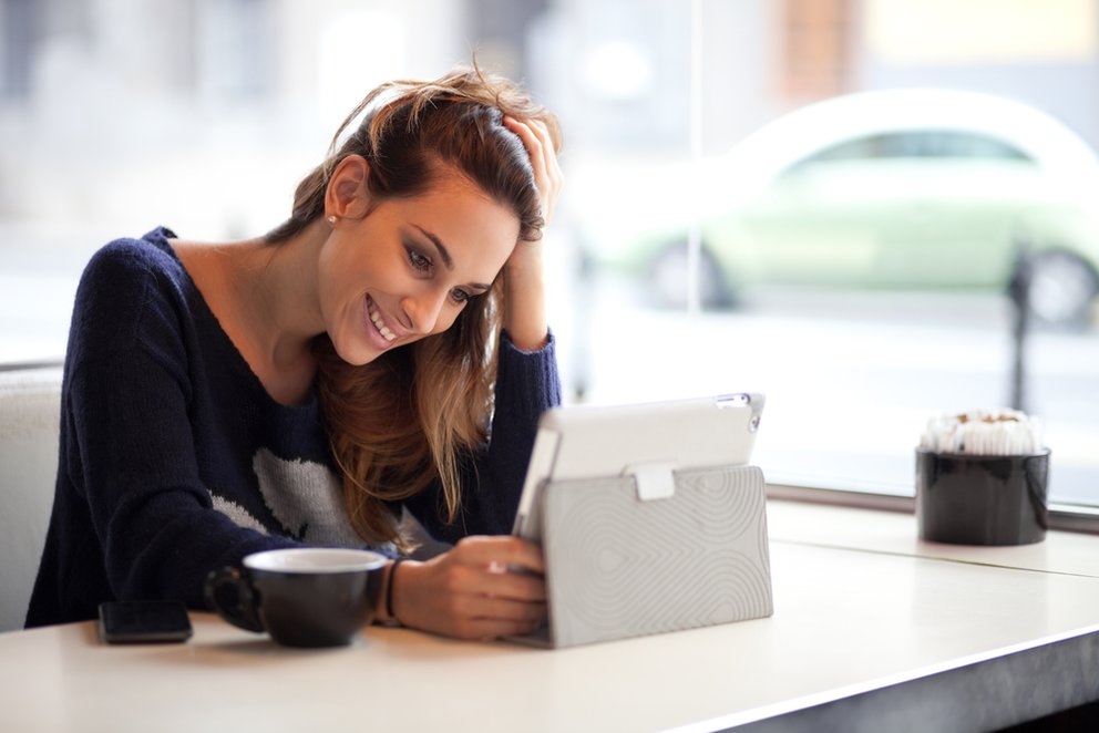 Happy young woman drinking coffee tea and using tablet