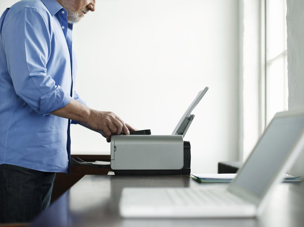 Side view midsection of a mature man using printer
