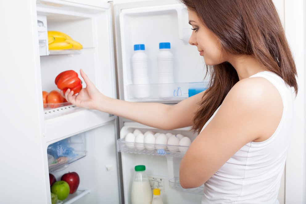 Woman searching in her fridge for fresh ingredients