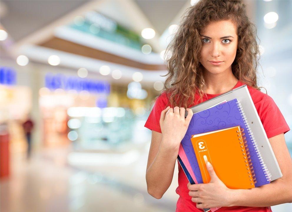Studentin mit Block und büchern im arm in der bibliothek