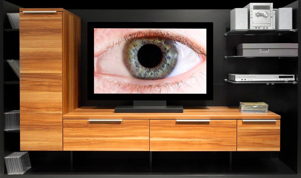Big Brother konzeptuelles bild einer schrankwand und einem beobachtendem auge dass aus dem fernseher herausschaut