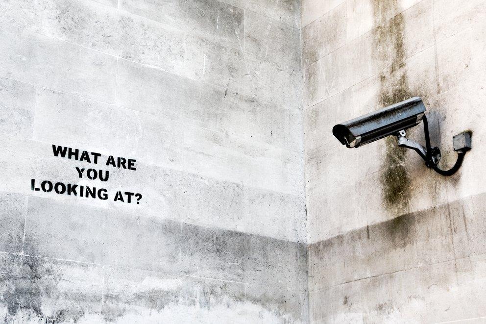 Berühmtes banksy graffitti betonwand mit installierter überwachungskamera und einer aufschrift an der wand die sagt what are you looking at?