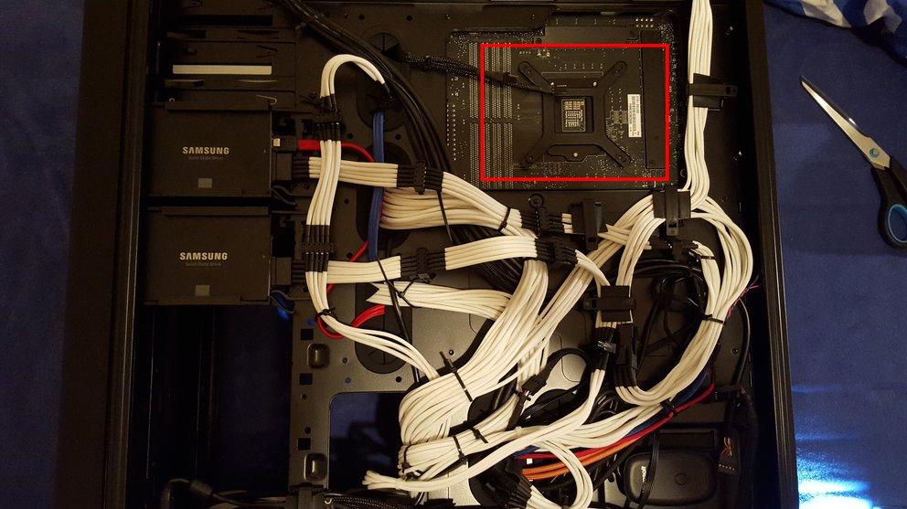 Manche Gehäuse ermöglichen die Montage der Kühler Rückplatte mit eingebautem Mainboard: Sie haben auf der Rückseite eine Öffnung, die den Zugang auf die Rückseite des Mainboards freigibt.