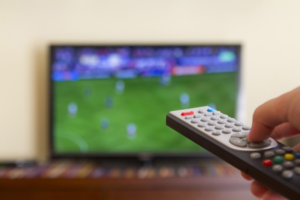 Watching a soccer match in the television, with a tv remote control in the hand