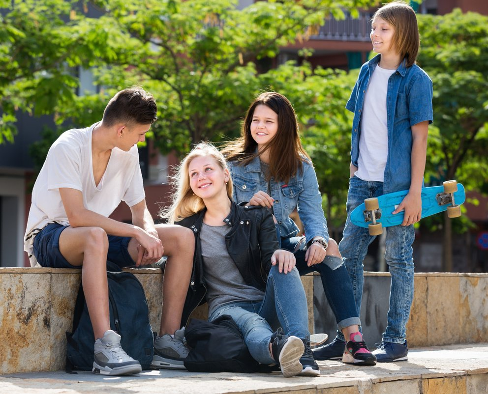 Group of smiling teenagers in park on summer day