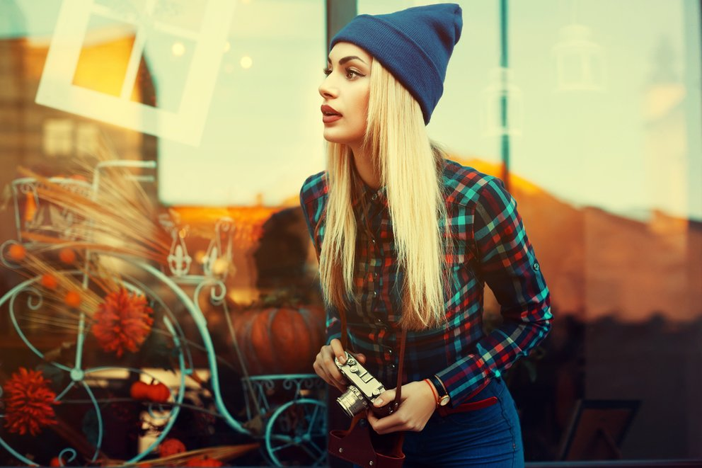Portrait of beautiful young playful hipster woman with old retro camera. Model looking aside. City lifestyle. Toned