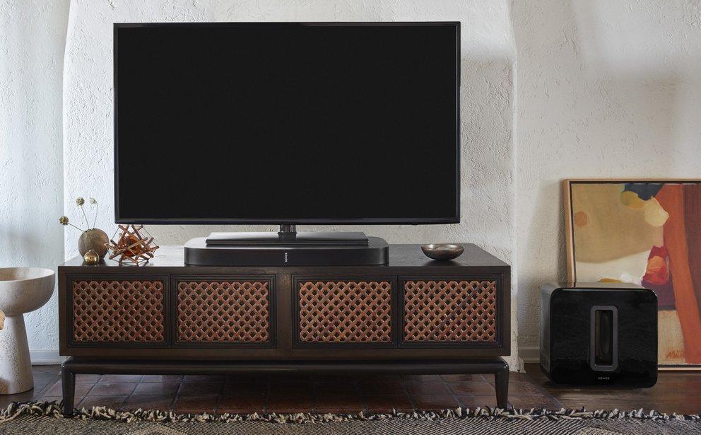Die PLAYBASE ist unter dem TV platziert und dient zugleich Stellfläche, rechts im Bild ist der optionale SUB zu sehen (Quelle: SONOS)