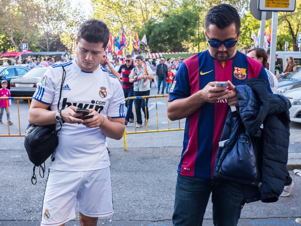 Two friends supporting Real Madrid and Barcelona watching their Smartphones