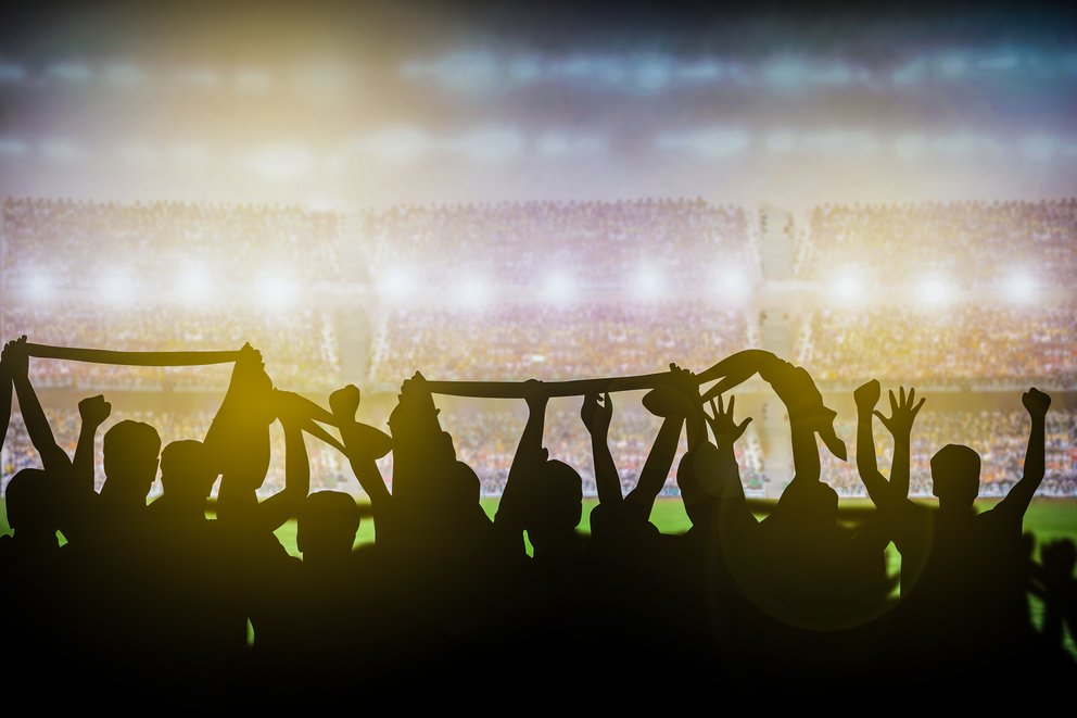 Silhouettes of soccer or rugby supporters in the stadium