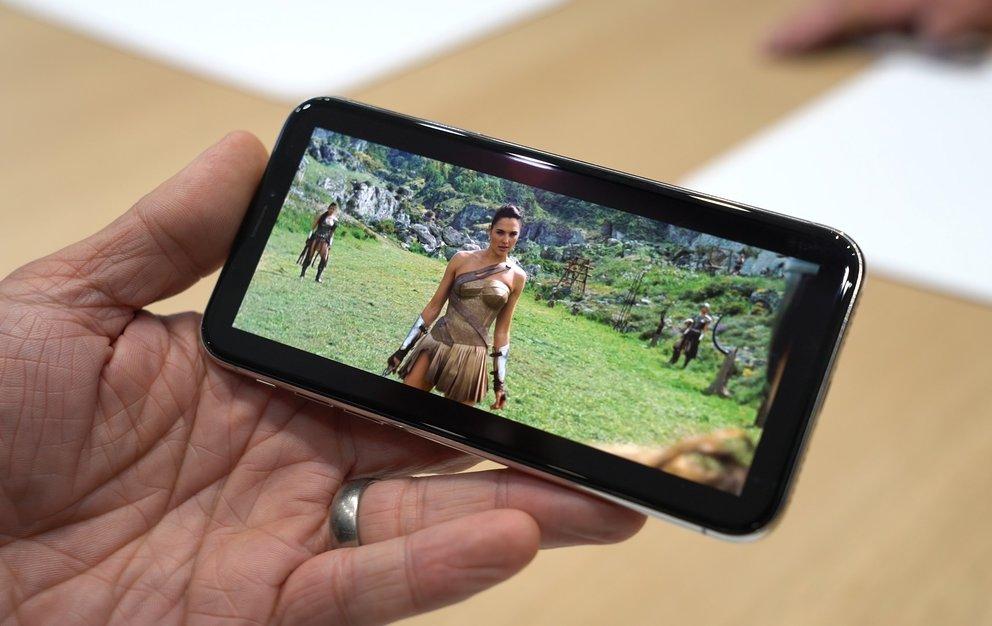 """Ein Filmtrailer (Wonderwoman) in der """"Windowboxed""""-Darstellung auf dem iPhone X. Der Notch ist nicht zu sehen, dafür schwarze Ränder um das Bild"""