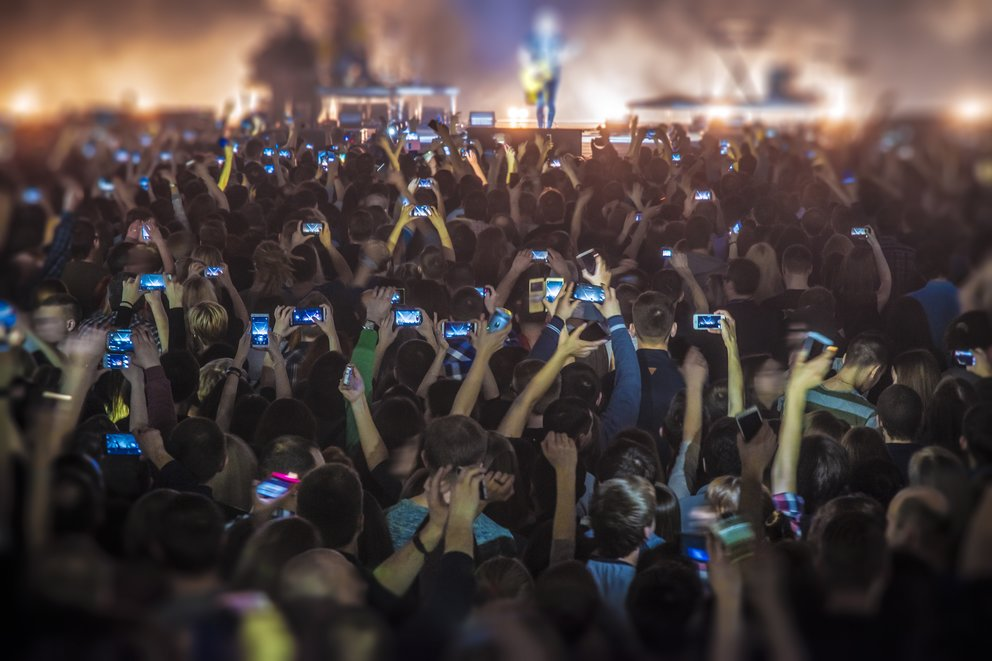 people at the concert with the phones shoot the show